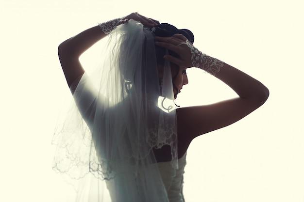 窓の近くに立っている美しい花嫁。白いウェディングドレスの少女。 Premium写真