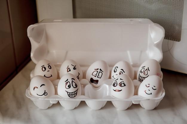Смайлики яйца. красит и чистит яйца на кухонном столе. Premium Фотографии