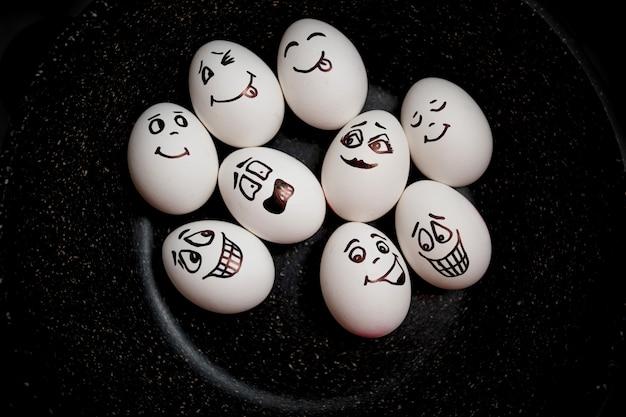 Эмоциональные яйца на сковороде. настоящие яйца с ручной росписью. копировать пространство Premium Фотографии