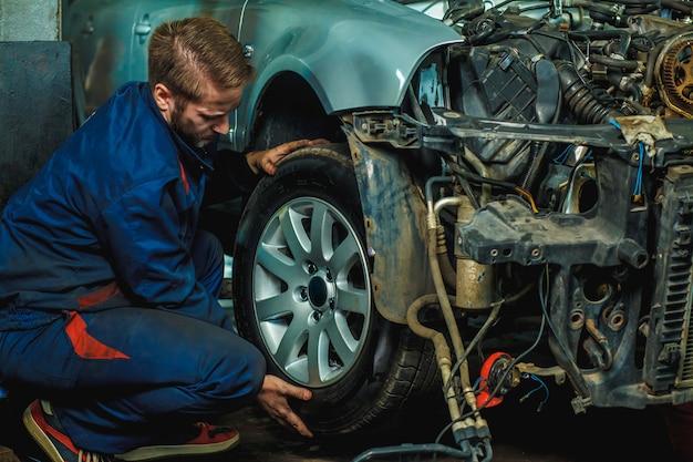 メカニックが車輪付き車両を修理しました。ガレージで車のタイヤを保持しているメカニック。 Premium写真