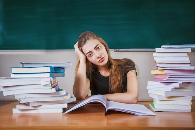 教室で勉強の本の巨大な山で机に座っている不満の女子学生 Premium写真