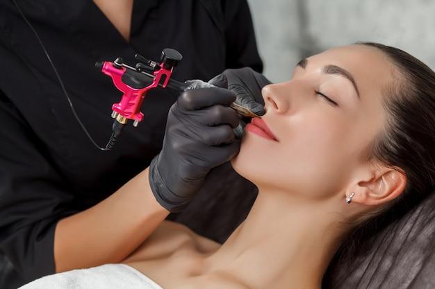 Перманентный макияж, нанесение на молодую девушку. крупный план. Premium Фотографии