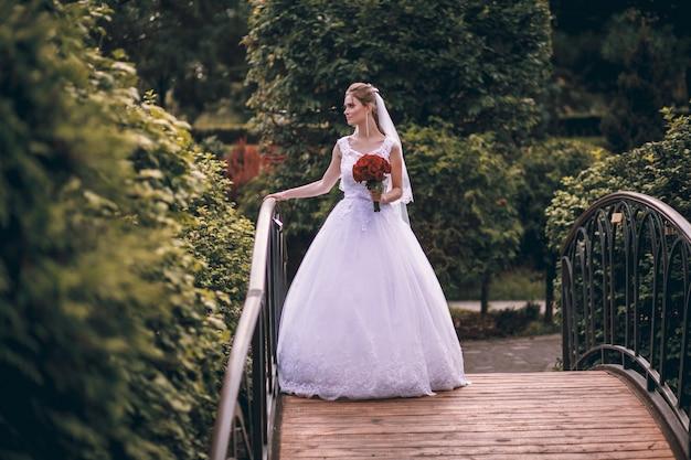 Красивая молодая белокурая невеста стоит на мостике в экзотическом парке, в длинном белом платье с букетом цветов в руках, гуляет после свадебной церемонии. Premium Фотографии