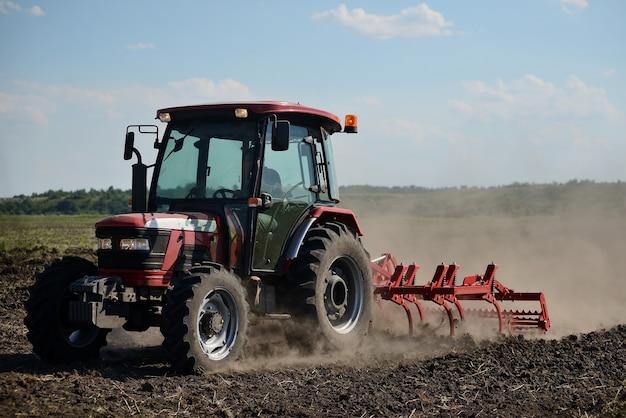 フィールド作業に真新しい赤いトラクター。土壌を耕し、植栽のための畑を準備するトラクター Premium写真