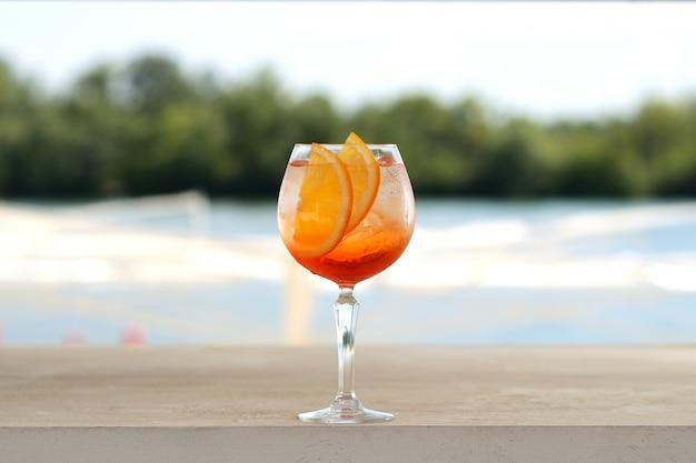 ガラスタンブラーに氷とオレンジのカクテル。花飾り付き Premium写真