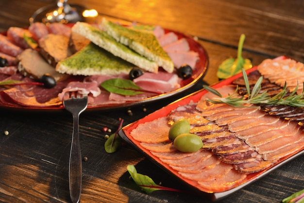 赤いプレートに揚げパンのスライスとソーセージ、ハモン、ハムの盛り合わせ。木製のテーブルの上 Premium写真
