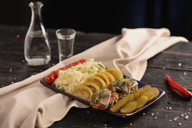 Соленая сельдь с маринованными овощами. на деревянном столе Premium Фотографии