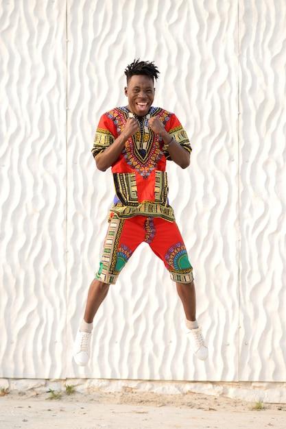 Счастливый молодой человек прыгает в нигерийской национальной одежде на белой стене Premium Фотографии