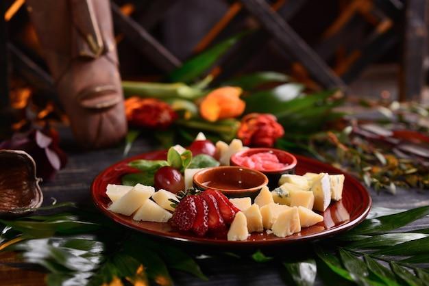イチゴ、ブドウ、ソースとチーズの盛り合わせ。赤いお皿に。花飾り付き Premium写真