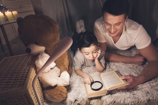 Отец и сын читают книгу ночью у себя дома. Premium Фотографии