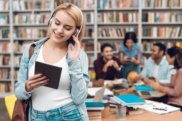 Белая девушка с помощью планшета, слушать музыку. Premium Фотографии
