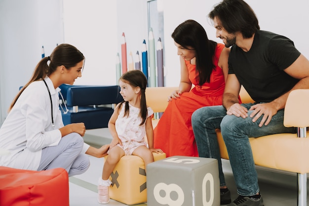 Дружелюбный доктор и семья в офисе педиатра Premium Фотографии