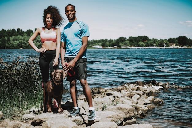 Афро-американская пара гуляет с собакой у реки Premium Фотографии