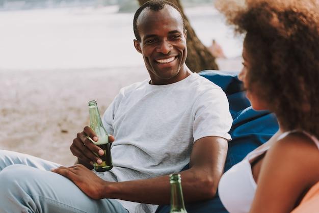 混血の新婚旅行カップルはビーチでビールを飲みます Premium写真