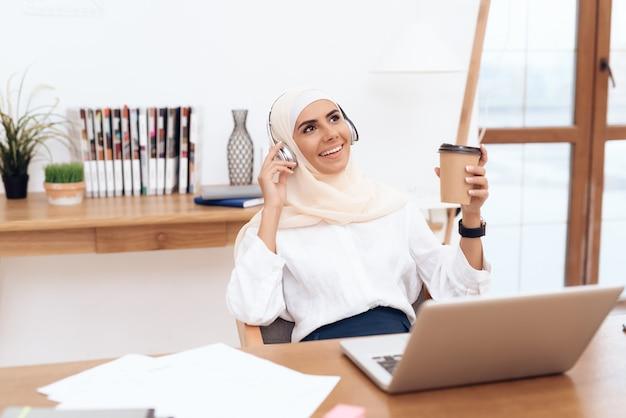 ヒジャーブの女性はヘッドフォンで音楽を聴きます Premium写真