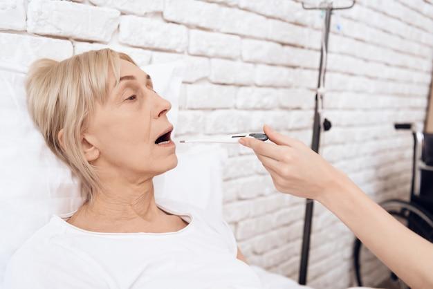 看護師は患者の体温計を口に当てます Premium写真