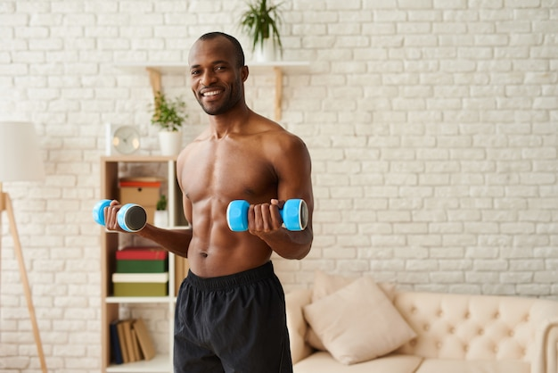 Афро-американский спортсмен, накачивание мышц гантелями. Premium Фотографии