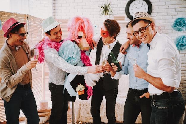 Веселые парни в галстуках-бабочках чокаются бокалами шампанского на вечеринке. Premium Фотографии