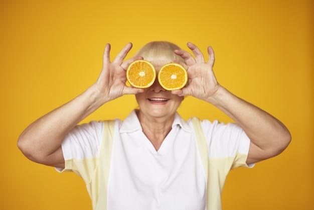 目の前で遊び心のある老婦人オレンジスライス。 Premium写真