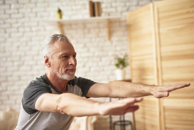 老人のストレッチとしゃがんだ家の練習。 Premium写真