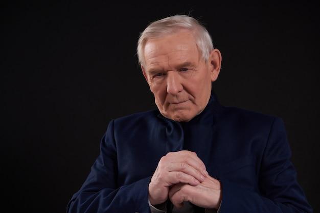 黒い背景に分離された不機嫌そうな老人の肖像画。 Premium写真