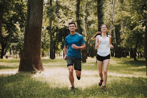 運動選手のカップルは緑豊かな公園で走っています。 Premium写真