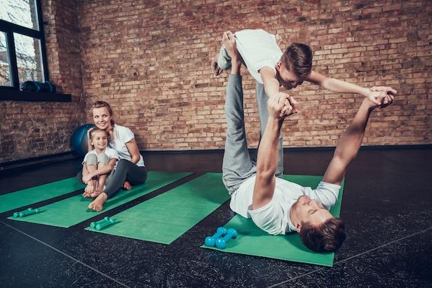 スポーツ家族のお父さんは足に息子のバランスをとっています。 Premium写真