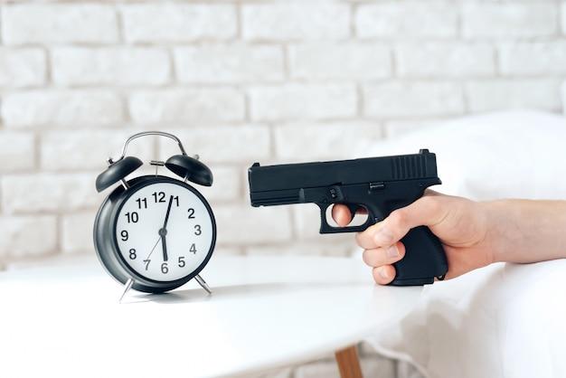 目を覚ます男は目覚まし時計で銃を目指しています Premium写真