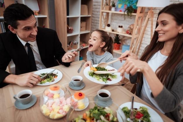 幸せなご家族一緒にテーブルで料理を食べる Premium写真