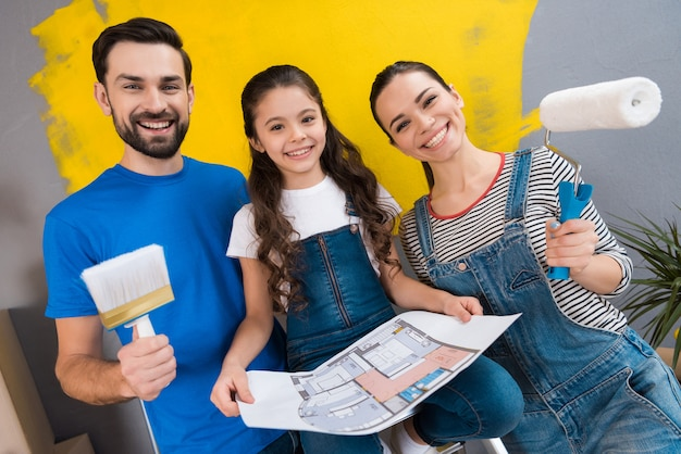 Молодая счастливая семья делает ремонт в доме на продажу Premium Фотографии