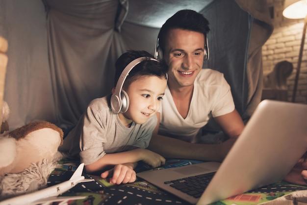 父と息子はラップトップで家族にスカイプで話しています。 Premium写真