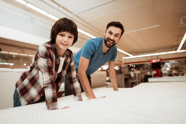 若い父親とマットレスを選ぶかわいい男の子 Premium写真