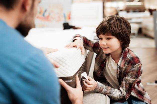 小さな男の子とハンサムな男のマットレスを選ぶ Premium写真