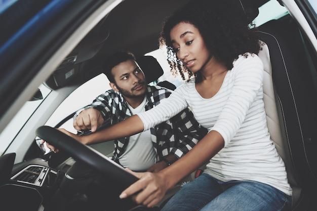 マッドガイはホイールで女性を見て新しい女性ドライバー Premium写真