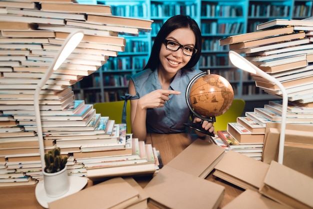 民族のアジアの女の子は図書館で地球を使用しています Premium写真