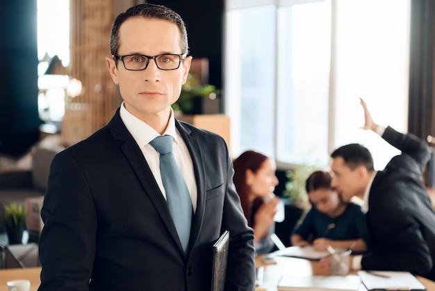 メガネで深刻な成人男性がオフィスの前に立つ Premium写真