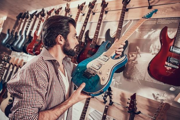 楽器の販売人は棚にエレガントなエレキギターを置きます Premium写真
