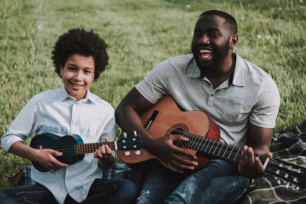 アフロの父とアフロの息子がピクニックにギターを弾きます。 Premium写真