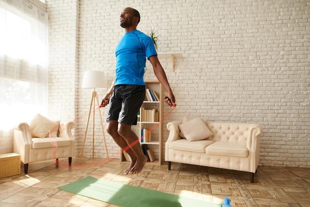 アフリカ系アメリカ人の運動選手は自宅で縄跳びでジャンプします。 Premium写真