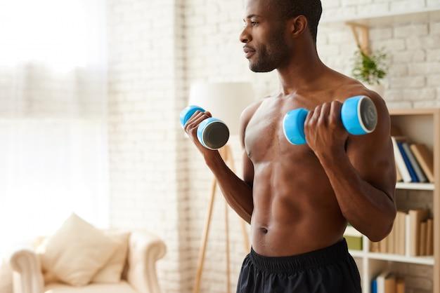 アフリカの運動選手がダンベルで筋肉をポンピング。 Premium写真