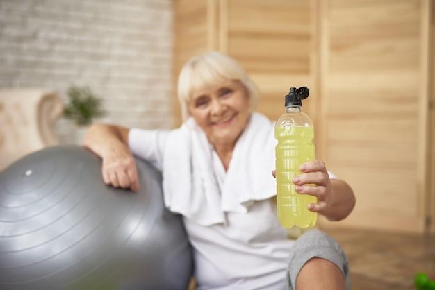 高齢者の女性は、スポーツをしているレモンデトックス水を持っています。 Premium写真