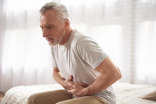 年配の男性は、朝のベッドで腹痛をしています。 Premium写真