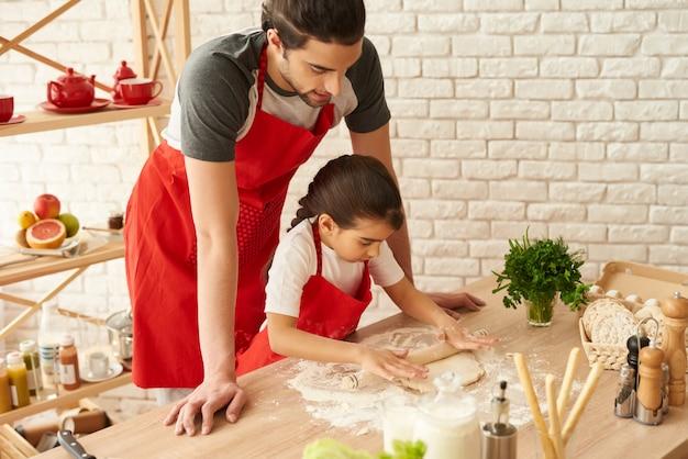 Отец и дочь раскатать тесто. тесто скалкой. Premium Фотографии