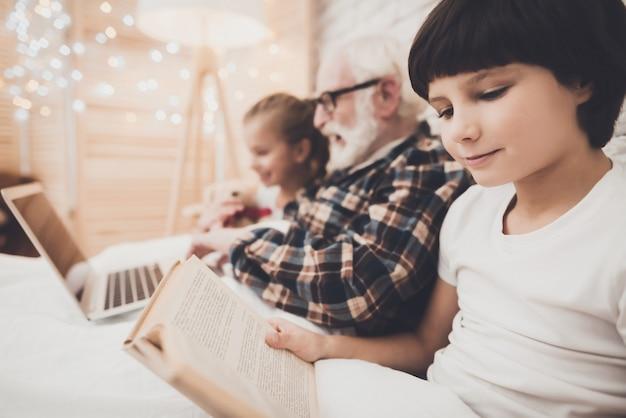 おじいちゃんと子供たちはベッドで映画を読んで見ています。 Premium写真