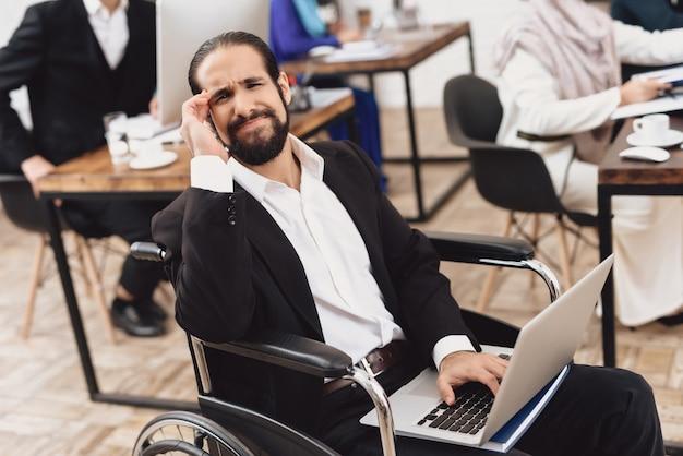 オフィスでラップトップ頭痛を持つ障害者労働者。 Premium写真