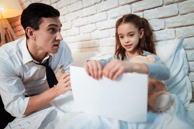 小さな娘は父親の書類を引き裂いています。 Premium写真