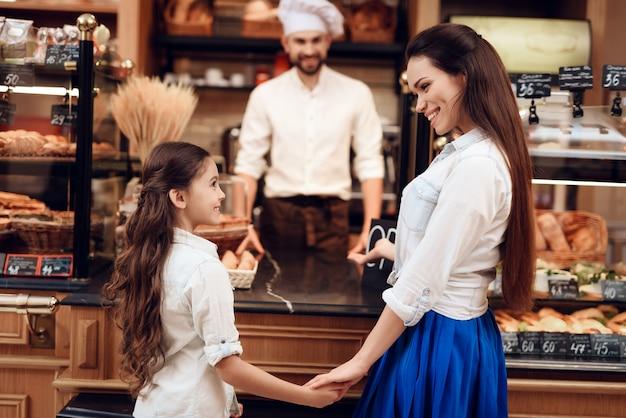 パン屋さんでパンを買う娘を持つ若い女。 Premium写真