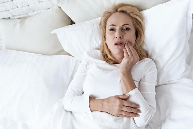 その女性は歯が痛い。彼女は気分が悪い。それは痛い。 Premium写真