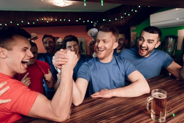青と赤のチームファンがスポーツバーでレスリング Premium写真