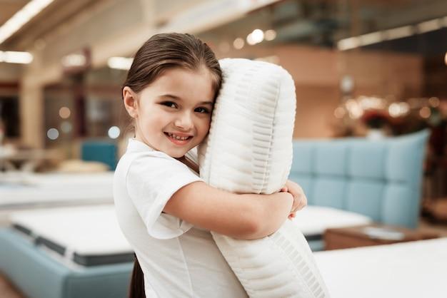 マットレス店で幸せな小さな女の子抱き枕 Premium写真